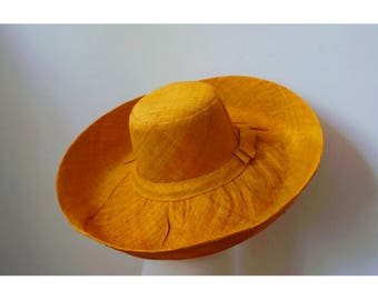 Great Sun Hat has wide brim finely handwoven raffia with a bow on the side, yellow