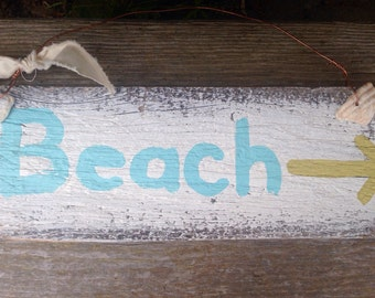 Beach sign with arrow and shells.