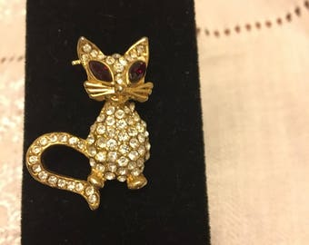 MEOW! Unmarked rhinestone cat with red gemstone eyes. Dress up any outfit with this brooch.