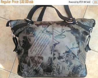 carelessly elegant, A large luggage bag, black back, face in dark gray print, outer zippered pocket and an inner tab and zippered pocket.