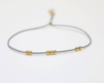 Tiny brass gold bead grey string bracelet minimalist jewelry stackable bracelet boho chic layered bracelet bohemian lucky bracelet baby gift