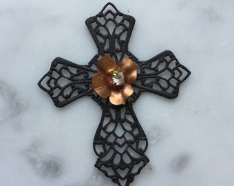 1 Filigree cross with patina copper colored flowers perched in the center with a small crystal rhinestone