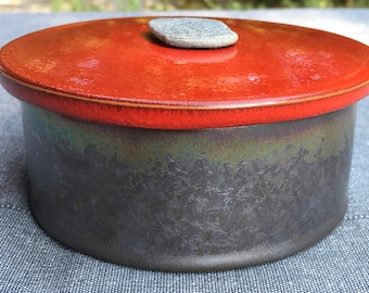 Glazed earthenware in red and black metal box