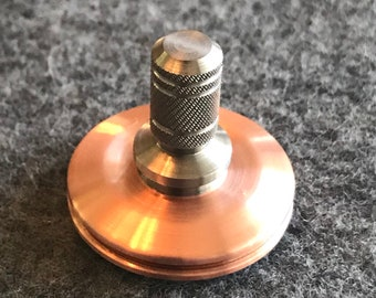 Spin Wright one inch diameter copper and titanium spinning top with a ceramic bearing.