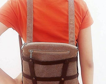 Backpack convertible to handbag with genuine leather decorative harness.