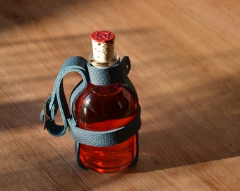 Bottle glass phial with leather straps