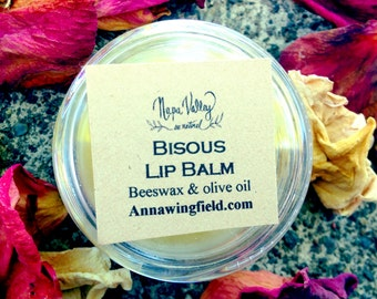 Bisous (kiss-in French) lip balm in 10ml plastic container.