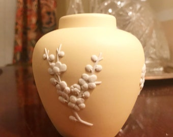 Wedgwood tan / pale yellow bud vase with white floral design.