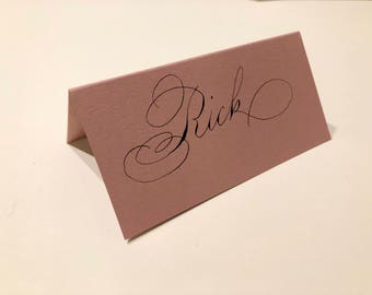 Dusty pink place cards in black ink traditional copperplate calligraphy. Bespoke custom handmade wedding tented cards blush gorgeous