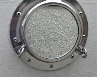 A superb polished metal ship's porthole mirror