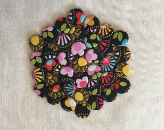 Hexagonal Kitchen Trivet with a Multi Colored Flower on Black Background Design