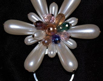 White flower with Multi colored rhinestone cluster center.;