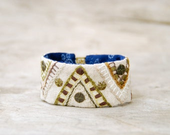 Hand embroidered bracelet. Textile bracelet cuff with embroidery and brass spangles