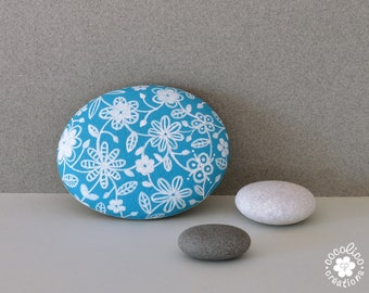 Pebble painted white flowers on a blue background