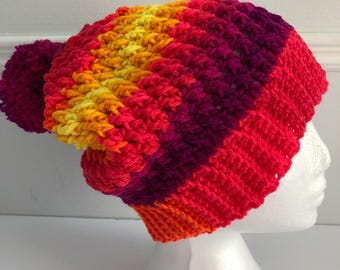 Slouchy  beanie hat with pompom in bright variegated yarn.