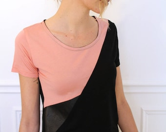 Short sleeve knit asymmetric top. Leather effect detail. Black and pink colors