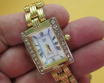 Vintage 7 inch gold tone watch with rhinstone sides clip closure marked ET used new battery