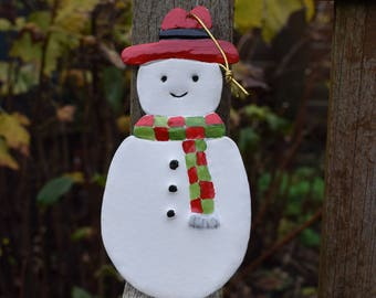 John the snowman with a red hat.