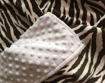 A zebra print in pink and brown minky blanket  ,The back is a pink minky dot.