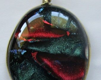 Dichronic Glass pendant. It is two by one and a quarter.  It is wrapped in brass.  It is red and turquoise.
