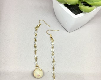 Long drop earrings on gold and bead chain