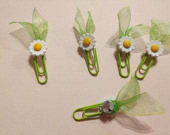 Just in time for spring! Little white and yellow Daisy's! All on green paper clips with little ribbon leaves!