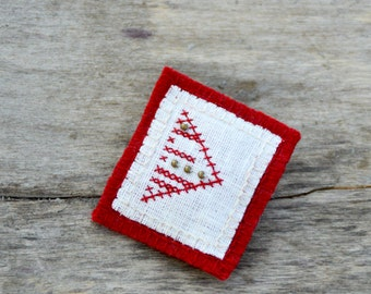 Hand embroidered textile brooch with antique brass beads. Red and white linen and woolen brooch.