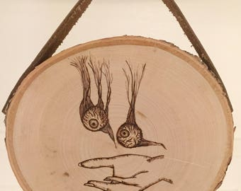 Wood burning hand catching eyes with leather strap.