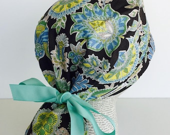Ponytail Scrub Cap scrub hat featuring a gray material with flowers in teal yellow and white with a matching ribbon