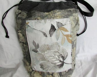 Cylinder shoulder bag made from remnants and scraps in earth tones with drawstring closure, many pockets with magnetic clasps