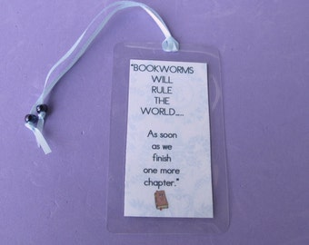 Bookmark with cute 'bookworm' quote.   Laminated bookmark finished with ribbon and glass beads.