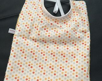 Child's bib has tie mixed colorful polka dots
