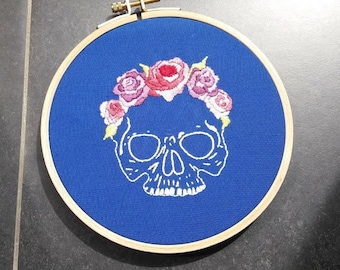 Skull with flowers on blue background