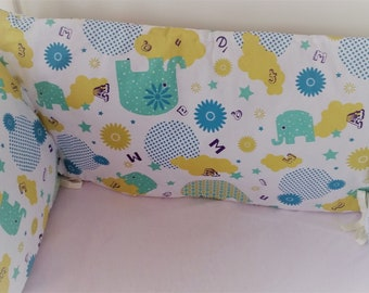 Round bed printed baby elephants and geometric patterns.