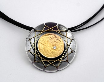 The web. A modern round gold and oxidized silver pendant with a diamond and a distinctive design that refers to halloween.