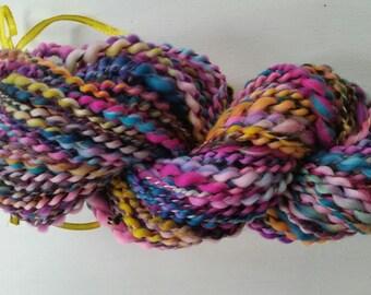 FUN skein of handspun wool with spinning wheel.