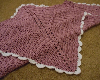 Hand crocheted baby blanket in soft pink and white yarn