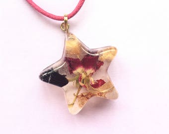 Preserved beetle and dried rose with cream flower petals in star-shaped transparent clear resin pendant charm