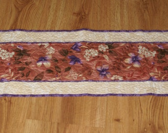 Quilted Table Runner made of fabric with purple and cream flowers with cream and tan accents against a salmon background