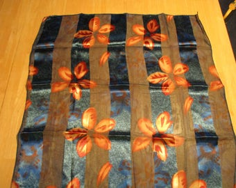This Luscoius, Peek-a-Boo scarf is adorned with shades of deep blue, rust, copper and apricot flower designs.