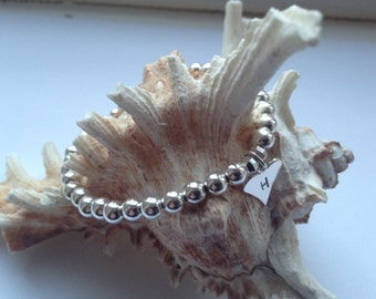 A sterling Silver beaded bracelet with a Sterling Silver Heart Charm.