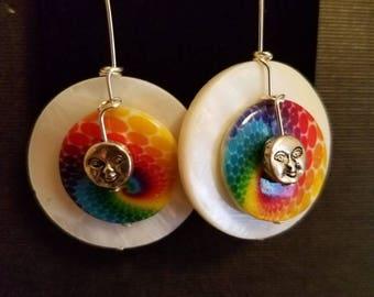 Moon faces on a rainbow swirl background