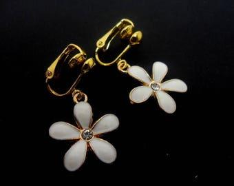 A pair of gold/white enamel flower themed clip on earrings. new.