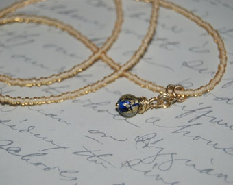 Gold Beige Necklace with Wire Wrapped Golden Blue Lampwork Glass Pendant.