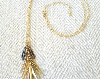 Gold tone necklace with bronze feather accent charms