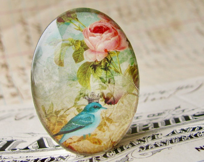 Aqua songbird with crown, from our Beautiful Birds collection of handmade glass cabochons, 40x30mm, oval cabochon, pink roses, blue bird