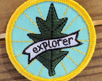 explorer - round embroidered iron-on patch featuring leaf