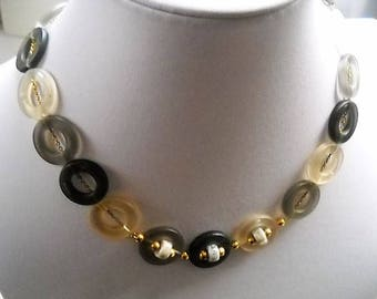 1970's  Fantasy necklace with circular motifs that repeat in three shades of gray. The necklace is threaded in a gold plated curve chain