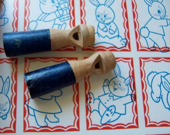 two tiny wooden whistles
