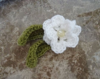 White crochet flower with green leaves brooch